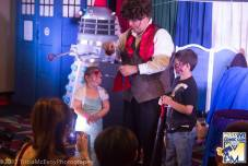 Two kids help the doctor while a Fezed Dalek watches